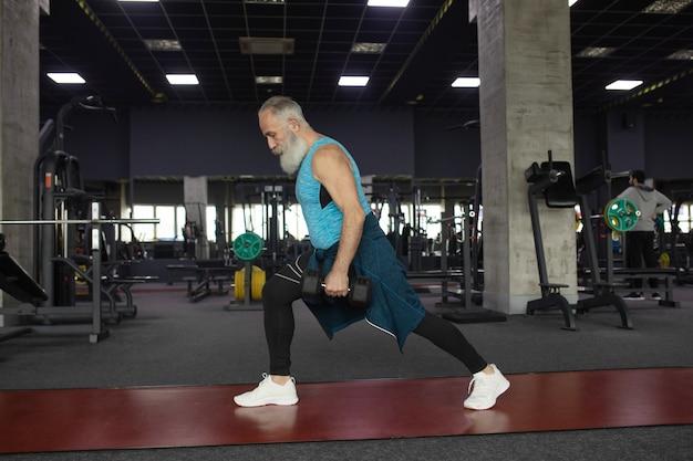 Starszy mężczyzna w odzieży sportowej w siłowni, poćwiczyć z ciężarami.