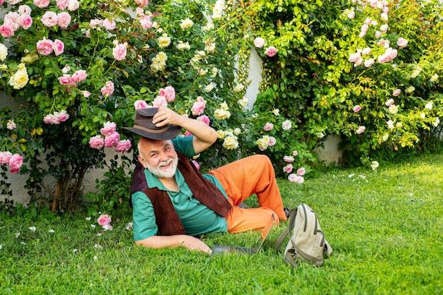 Starszy mężczyzna w ogrodzie róż. ogrodnicy z wiosennych kwiatów. dziadek pracujący w ogrodzie.