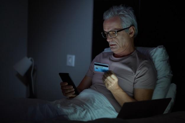 Starszy mężczyzna w okularach, leżąc na łóżku, płacąc online kartą kredytową za pomocą swojego telefonu komórkowego jest późny wieczór
