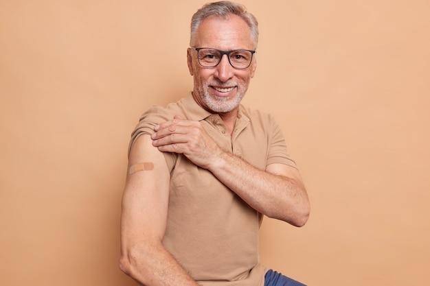 Starszy mężczyzna w okularach pokazuje oklejone ramię po otrzymaniu szczepionki na koronawirusa, ciesząc się, że czuje się bezpiecznie i chroniony na tle brązowej ściany