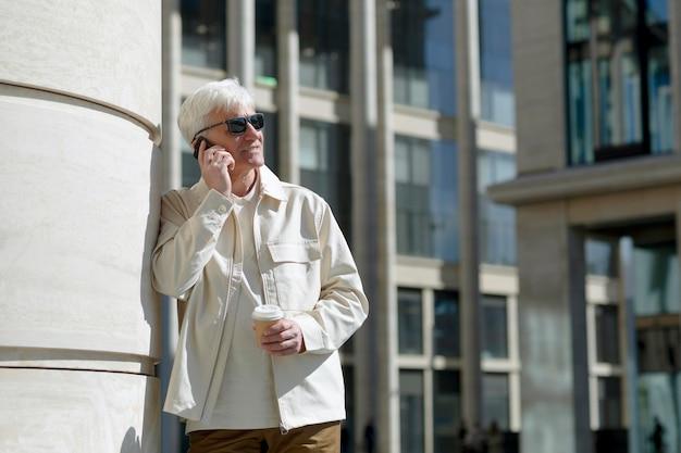 Starszy mężczyzna w okularach przeciwsłonecznych na zewnątrz w mieście rozmawia przez telefon