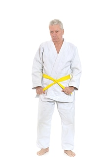 Starszy mężczyzna w pozie karate na białym tle