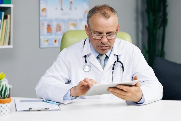 Starszy mężczyzna w średnim wieku, lekarz w białym mundurze, trzymający w rękach cyfrowy tablet komputerowy, zarządzający wizytami pacjentów.