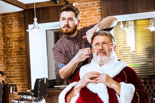 Starszy mężczyzna w stroju świętego mikołaja goli swojego osobistego mistrza w salonie fryzjerskim przed świętami bożego narodzenia
