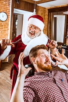 Starszy mężczyzna w stroju świętego mikołaja pracuje jako osobisty mistrz z nożyczkami w salonie fryzjerskim przed świętami bożego narodzenia