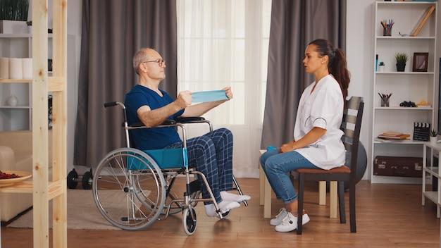Starszy mężczyzna w treningu na wózku inwalidzkim z powodu urazu mięśni z terapeutą. niepełnosprawna niepełnosprawna osoba starsza z pracownikiem socjalnym w okresie rekonwalescencji terapia rehabilitacyjna fizjoterapia opieka zdrowotna pielęgniarstwo emerytura ho