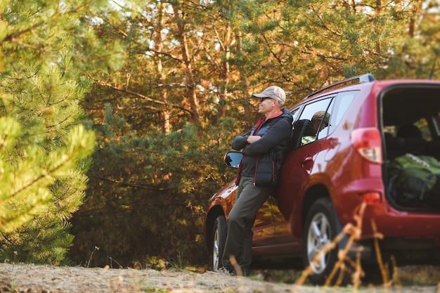 Starszy mężczyzna w turystycznym ubraniu i okularach przeciwsłonecznych w lesie w pobliżu suv-a