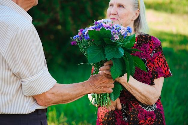 Starszy mężczyzna w wieku 80 lat daje kwiaty swojej żonie