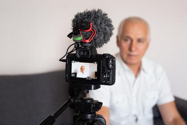 Starszy mężczyzna wideo blogger patrząc na aparat fotograficzny w domu