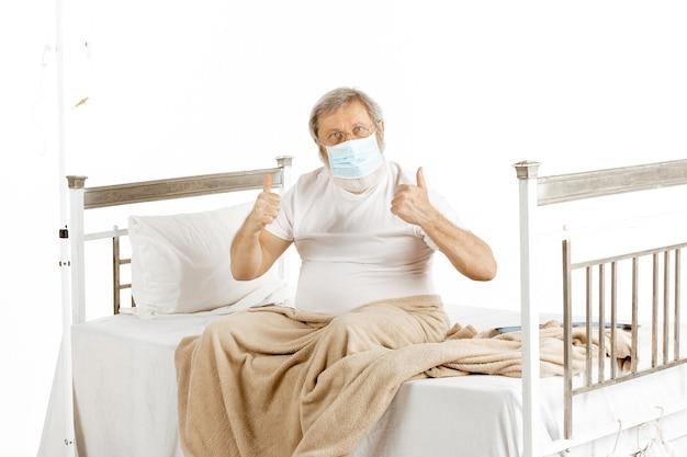 Starszy mężczyzna wraca do zdrowia w szpitalnym łóżku na białym tle