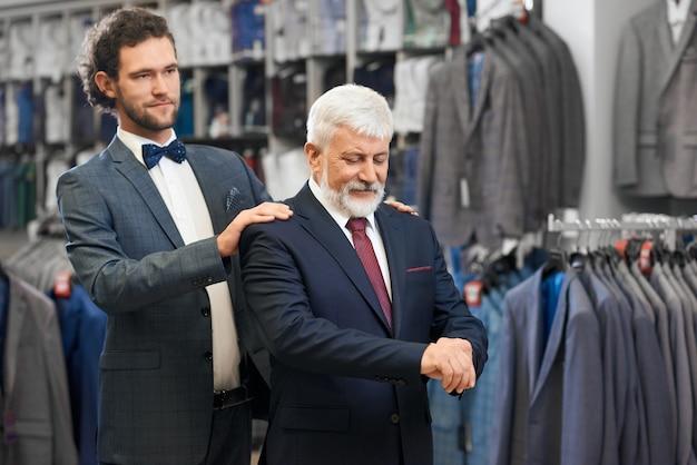 Starszy mężczyzna wybiera kostiumy z młodym przyjacielem.