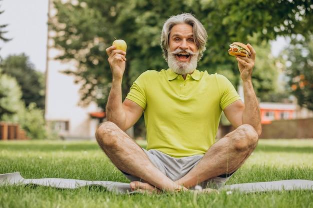 Starszy mężczyzna wybiera między burgerem a jabłkiem