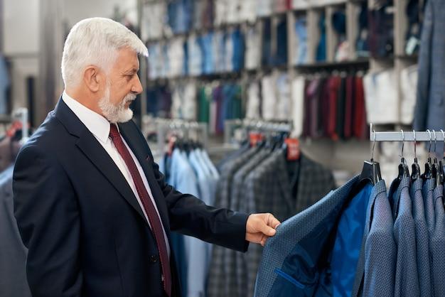 Starszy mężczyzna wybiera nowe stylowe kostiumy.