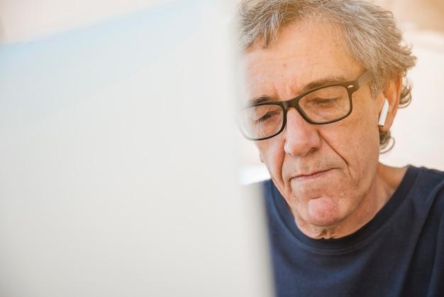 Starszy mężczyzna z białą bluetooth słuchawką w jego ucho używać laptop