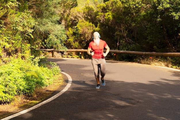 Starszy mężczyzna z białą brodą robi bieganie na świeżym powietrzu na naturze przy drodze