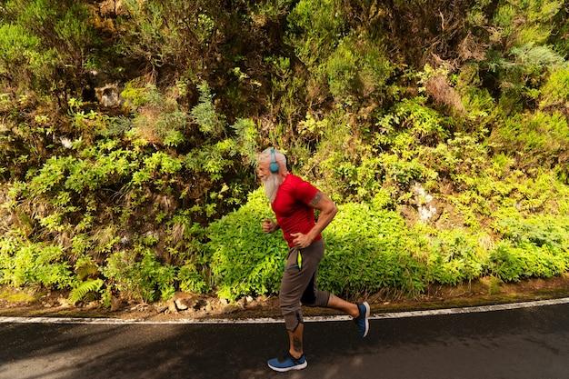 Starszy mężczyzna z białą brodą robi bieganie na świeżym powietrzu na naturze