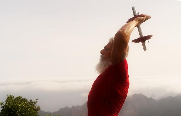 Starszy mężczyzna z białą brodą robi ćwiczenia sportowe z dumbell na świeżym powietrzu, bliska widok, piękna natura w tle
