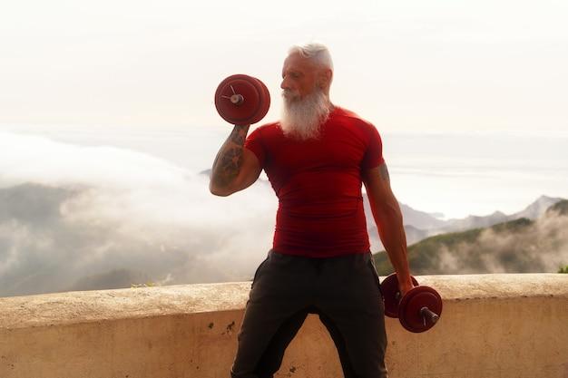 Starszy mężczyzna z białą brodą robi ćwiczenia sportowe z dwoma hantlami na świeżym powietrzu, bliska widok, koncepcja zdrowego i szczęśliwego stylu życia