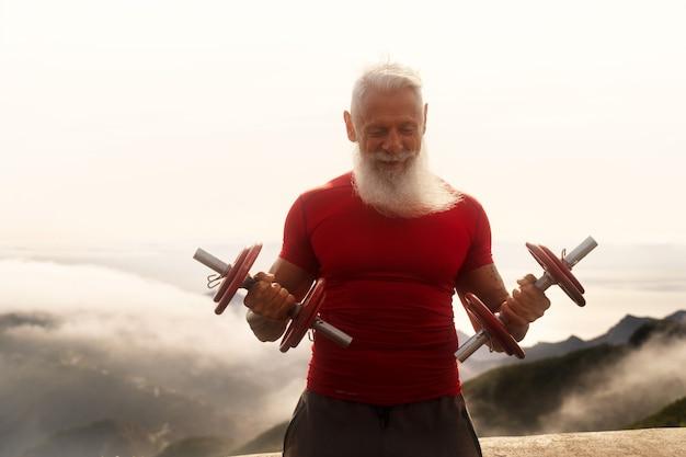 Starszy mężczyzna z białą brodą robi ćwiczenia sportowe z hantlami na świeżym powietrzu, bliska widok, koncepcja zdrowego i szczęśliwego stylu życia