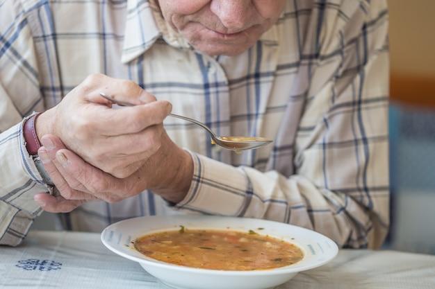 Starszy mężczyzna z chorobą parkinsona trzyma łyżkę w obu rękach.