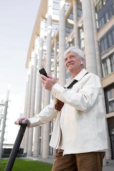 Starszy mężczyzna z elektryczną hulajnogą w mieście za pomocą smartfona i słuchawek