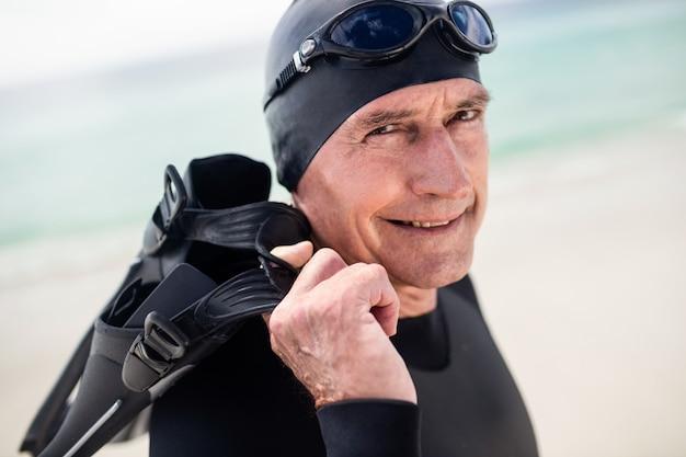 Starszy mężczyzna z flipper pozycją na plaży