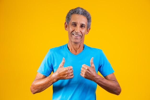 Starszy mężczyzna z kciukiem do góry dając kciuk w górę.
