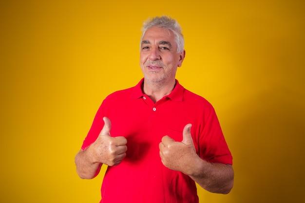 Starszy mężczyzna z kciukiem do góry i znakiem ok
