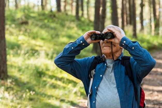 Starszy mężczyzna z lornetką na zewnątrz przyrody