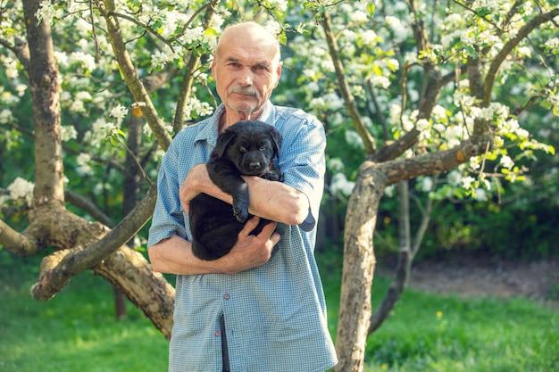 Starszy mężczyzna z małym czarnym szczeniakiem labradora na zewnątrz