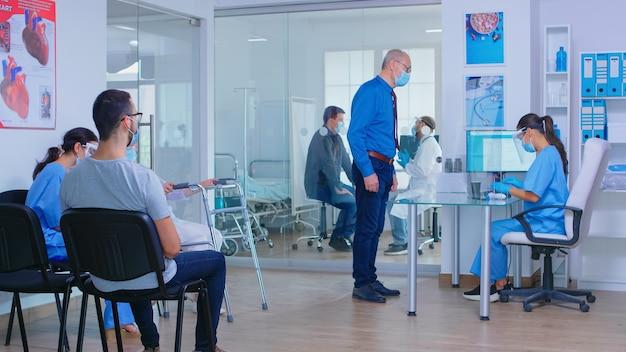 Starszy mężczyzna z maską na covid-19 w recepcji szpitala rozmawia z pielęgniarką. lekarz z pacjentem w sali egzaminacyjnej. niepełnosprawna dojrzała kobieta z balkonikiem w poczekalni.