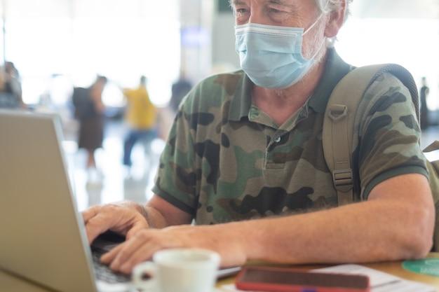 Starszy mężczyzna z maską na twarz pije kawę i korzysta z laptopa na lotnisku, czekając na wejście na pokład