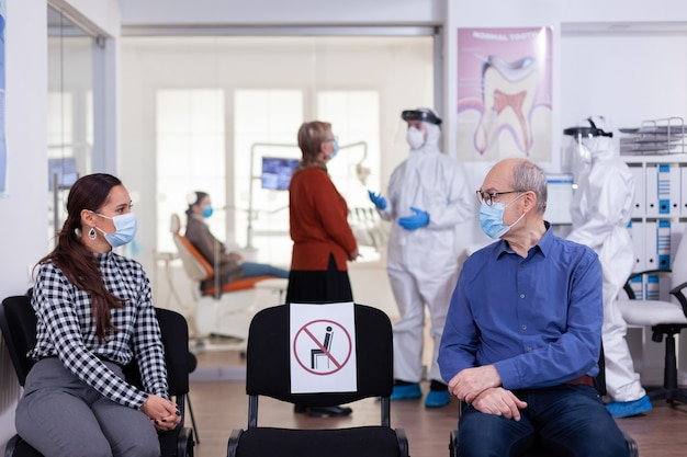 Starszy mężczyzna z maską na twarz rozmawia z pacjentką w klinice stomatologicznej w poczekalni, zachowując dystans społeczny podczas globalnej pandemii z koronawirusem