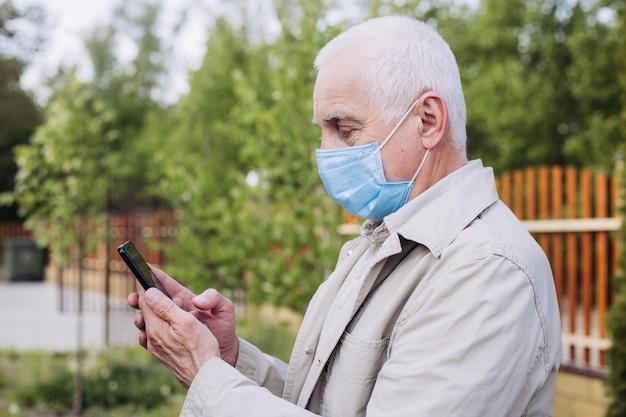 Starszy mężczyzna z maski medyczne za pomocą telefonu do wyszukiwania wiadomości. zatrzymaj infekcję, mężczyzna nosić maskę przeciw chorobom zakaźnym i grypie. pojęcie opieki zdrowotnej.