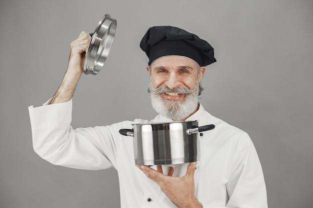 Starszy mężczyzna z metalową patelnią. szef kuchni w czarnym kapeluszu. profesjonalne podejście do biznesu.