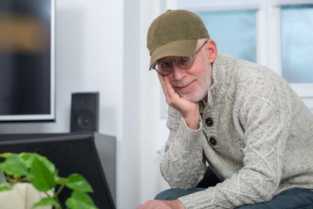 Starszy mężczyzna z nakrętką używać laptop w domu
