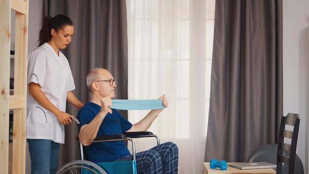 Starszy mężczyzna z niepełnosprawnością na wózku inwalidzkim robi ćwiczenia regeneracyjne z terapeutą. osoba starsza niepełnosprawna niepełnosprawna z pracownikiem socjalnym w okresie rekonwalescencji terapia pomocnicza fizjoterapia służba zdrowia pielęgniarstwo