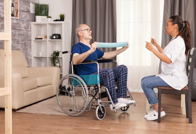 Starszy mężczyzna z niepełnosprawnością na wózku inwalidzkim wykonujący ćwiczenia regeneracyjne z taśmą oporową