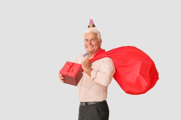 Starszy mężczyzna z prezentem na boże narodzenie i torbą świętego mikołaja na jasnej powierzchni