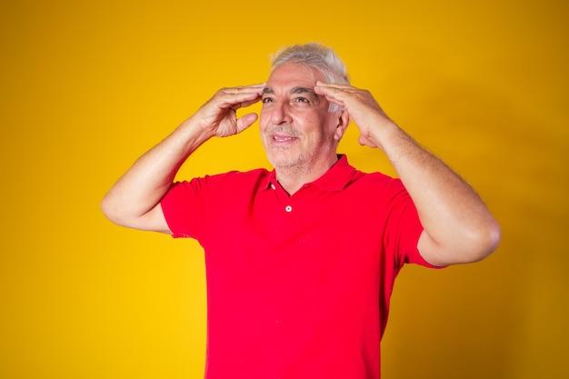 Starszy mężczyzna z ręką na głowie z pojęciem choroby alzheimera lub zapomnienia, a nawet bólu głowy