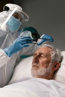 Starszy mężczyzna z respiratorem obok lekarzy