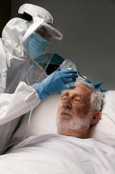 Starszy mężczyzna z respiratorem w szpitalnym łóżku