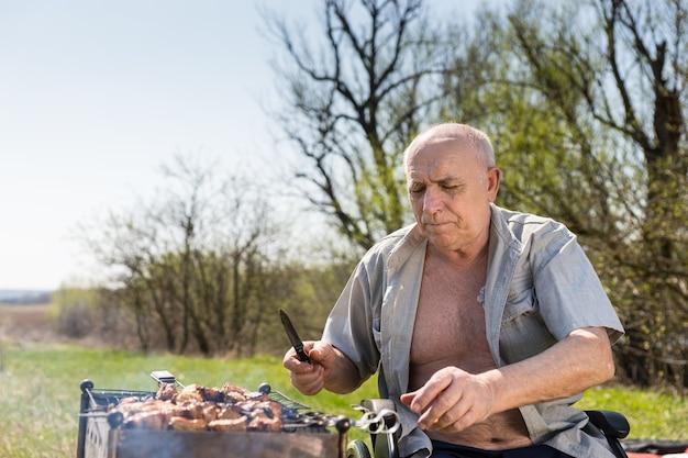 Starszy mężczyzna z rozpiętą koszulą, trzymając nóż, siedząc na wózku inwalidzkim podczas grillowania w parku w bardzo gorący poranek.