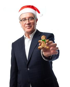 Starszy mężczyzna z santa hat pokazując pierników