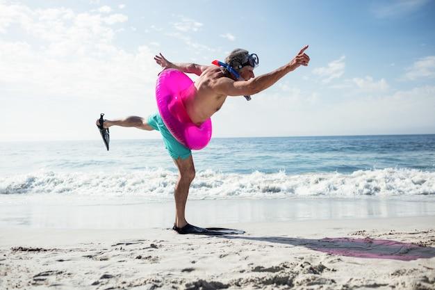 Starszy mężczyzna z sprzęt do nurkowania i nadmuchiwany pierścień, ciesząc się z wakacji