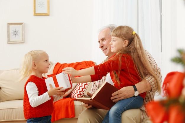 Starszy mężczyzna z wnuczkami siedzący na kanapie w salonie