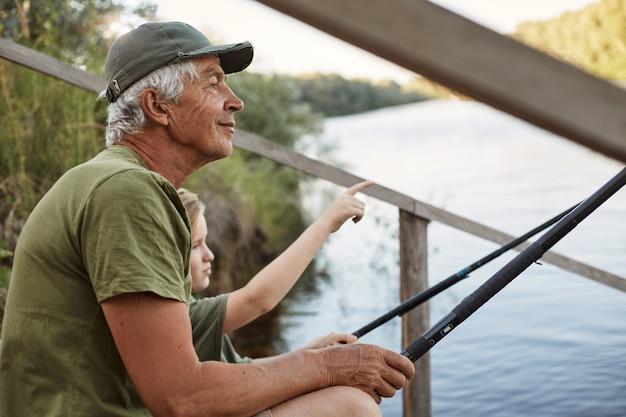 Starszy mężczyzna z wnukiem siedzi na drewnianym pontonie z wędkami w rękach, ciesząc się piękną przyrodą, mały chłopiec wskazując na coś palcem.
