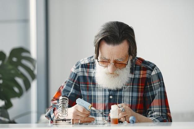 Starszy mężczyzna z wyposażeniem do lutowania. pracować w domu.