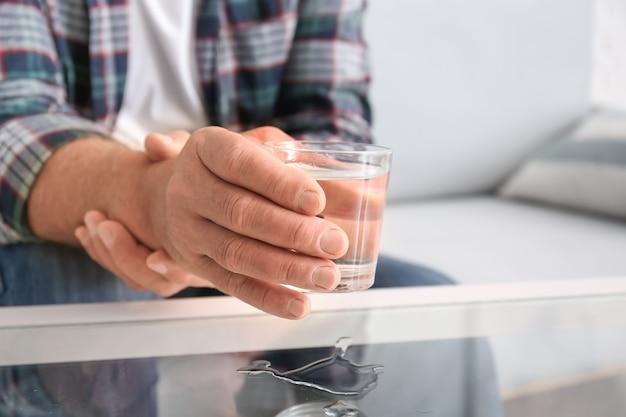Starszy mężczyzna z zespołem parkinsona, biorąc szklankę wody ze stołu, zbliżenie