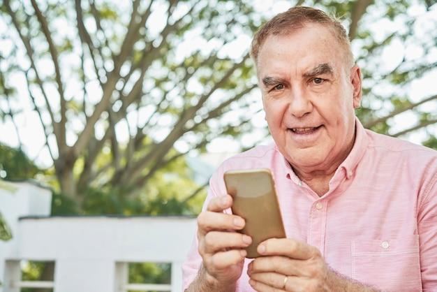 Starszy mężczyzna za pomocą aplikacji mobilnej